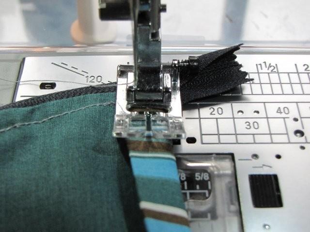 Das Schrägband zur Hälfte unter die offene Unterseite des Täschchens legen, umklappen und entlangnähen. Wenn der Reißverschluß zu lang ist: Einen Stopp am Reißverschluß mit der Hand einnähen und den überstehenden Teil mit der Zackenschere abschneiden.