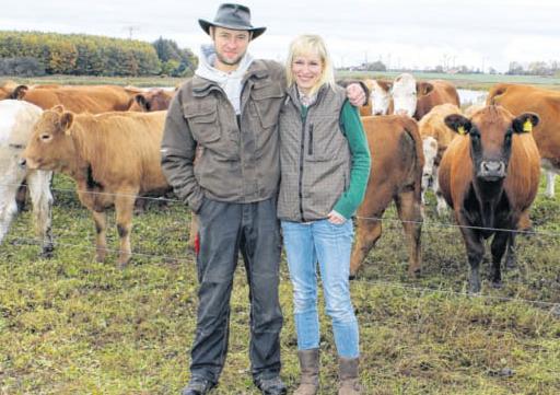 Inhaber Marc und Ulrike Nettebrock mit den Rindern am Eixener See