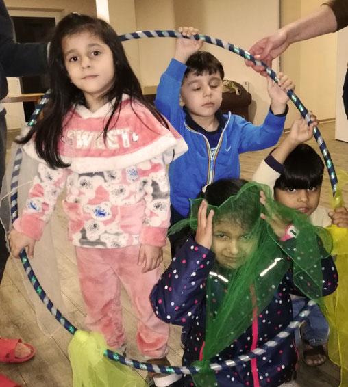 Mehrere Kinder sitzen in einem Hula-Hoop-Reifen und haben bunte Tücher in der Hand.