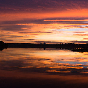 Variations of Red, beautiful colorful red and orange sunset at a lake with reflections close to Hundiksvall, Sweden