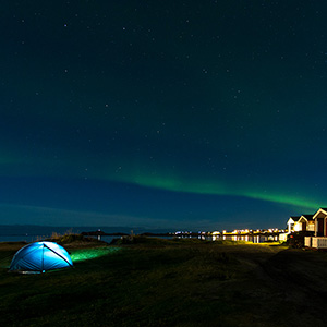 Illuminated tent and Aurora Borealis Northern Lights, Ramberg Beach, Lofoten, Norway