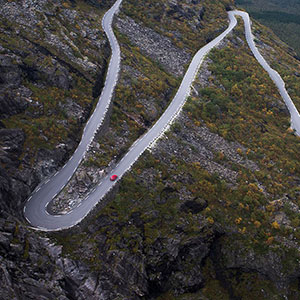 Serpentines @ Trollstigen viewpoint with a solitaire red car, Norway, Scandinavia