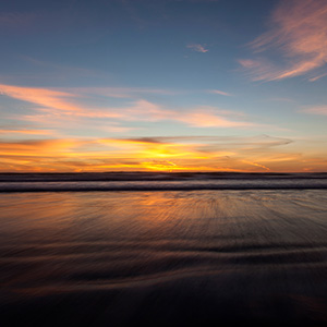 South Pacific Ocean Sunset with warm Colors and blurred Waves, New Zealand