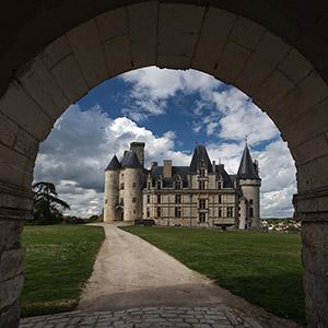 Chateau de la Rochefoucauld seen through a stone arch, Southern France