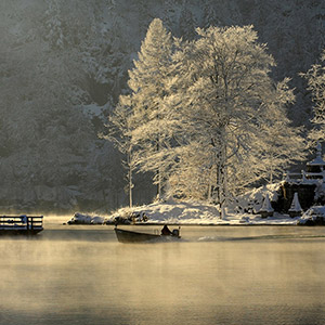 Early Morning, Boat in the morning fog at the beautiful Koenigssee with snow and ice in the trees, Bavaria, Germany
