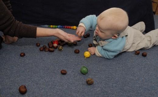 Therapiesituation Heilpädagogik: Kind greift eine Kastanie