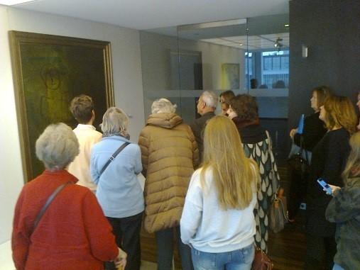 Des visiteurs pris en photo devant des tableaux de l'exposition Belfius