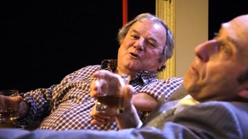 Photo de deux acteurs buvant un verre assis dans un canapé