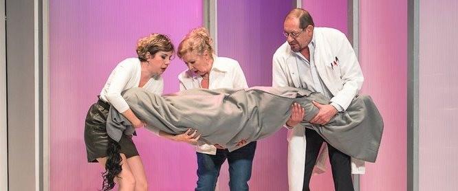 Photo de 3 acteurs portant un corp enroulé dans un drap