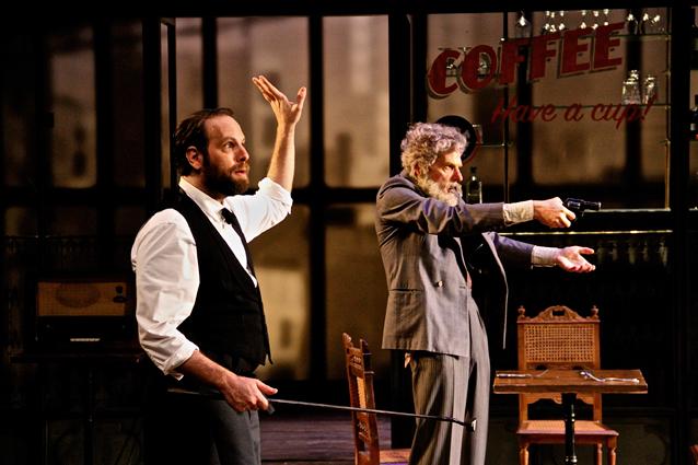 Deux des acteurs de la pièce sur scène dans le décors d'un bar