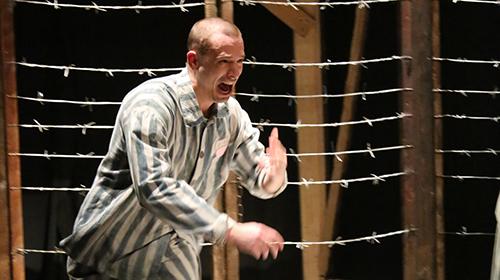 Max en tenue de prisonnier enfermé dans un camp de concentration.