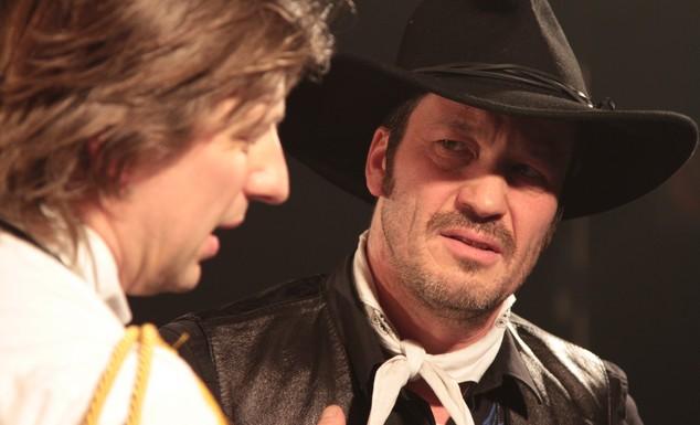 Deux acteurs de la pièce sur scène dont l'un habillé en cowboy
