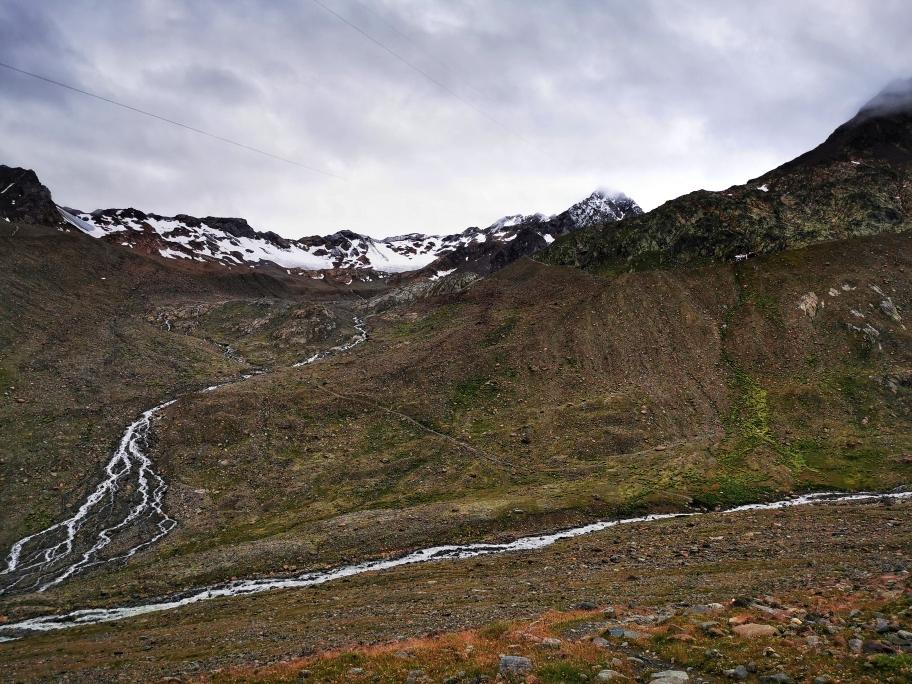 Oben links die Guslarspitzen, oben rechts kommt die Hütte in Sicht. Zunächst muss unten aber der Gletscherbach überquert werden