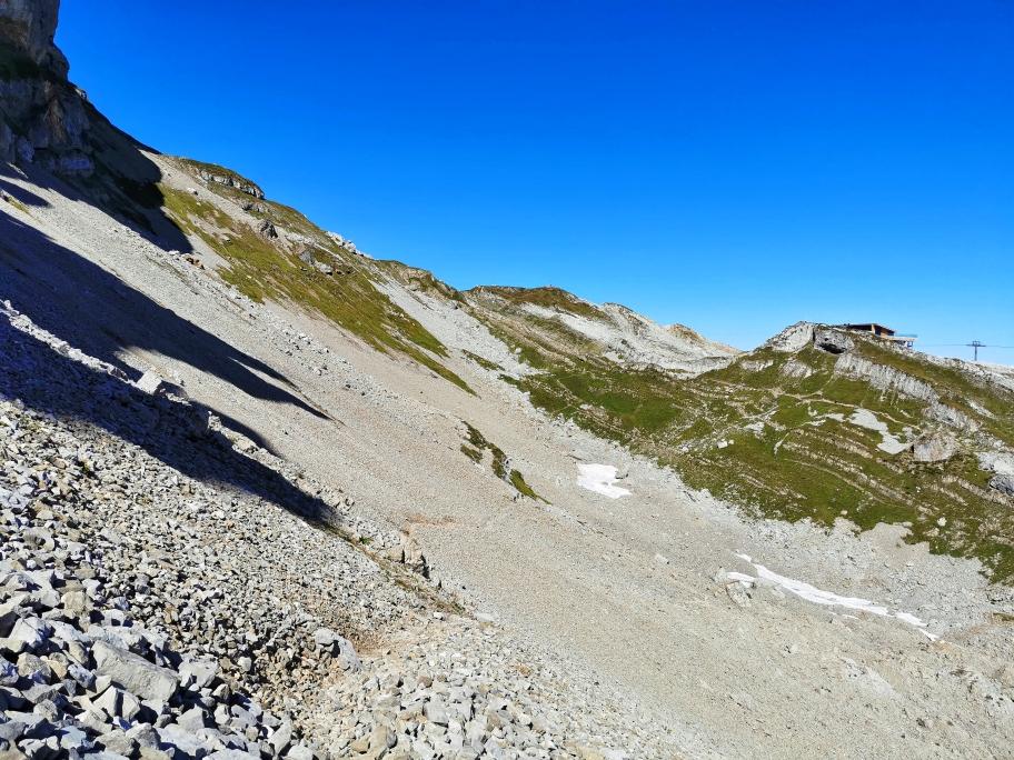 Im Schotter geht es leicht absteigend hinunter in die Ifenmulde, links oben der Gipfel