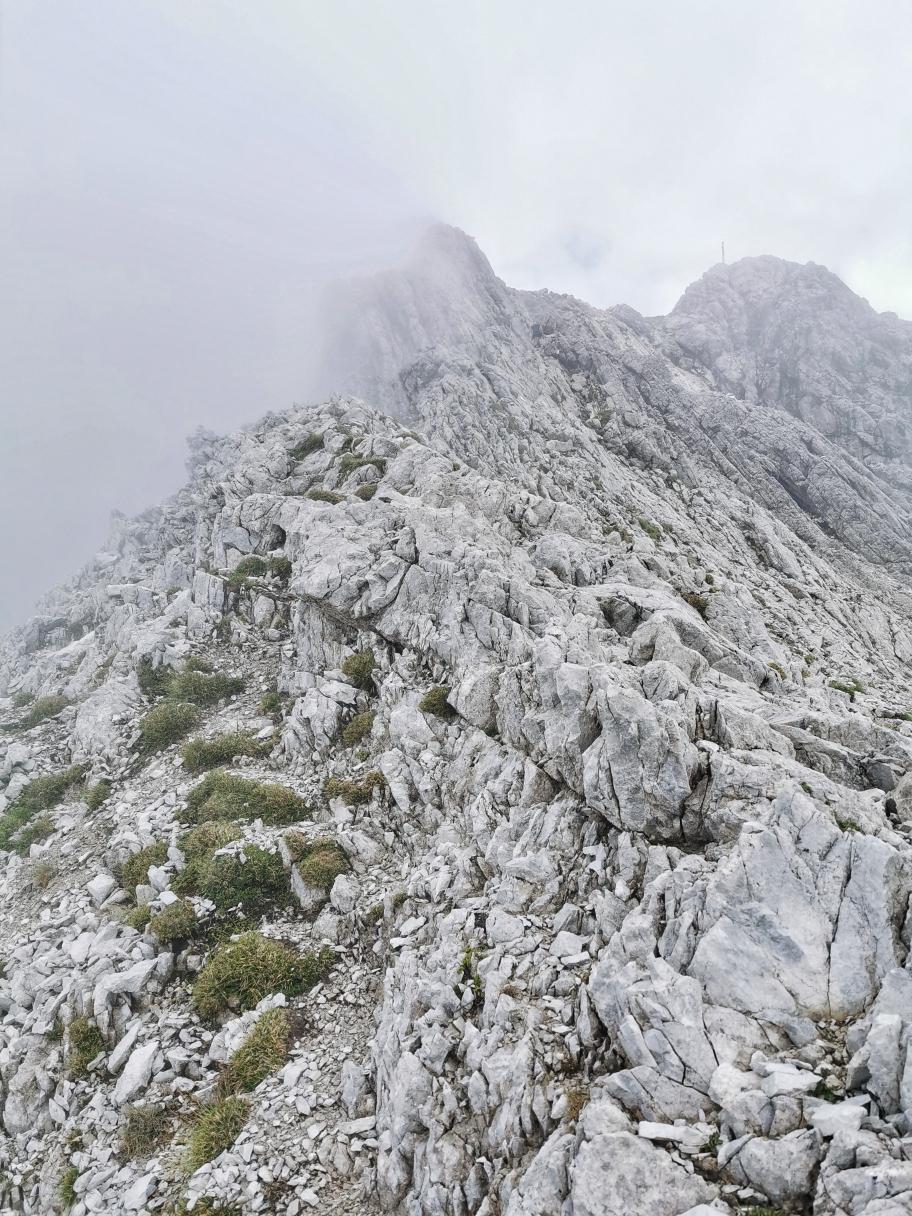 Auf dem Gipfelgrat, das Kreuz noch in den Wolken