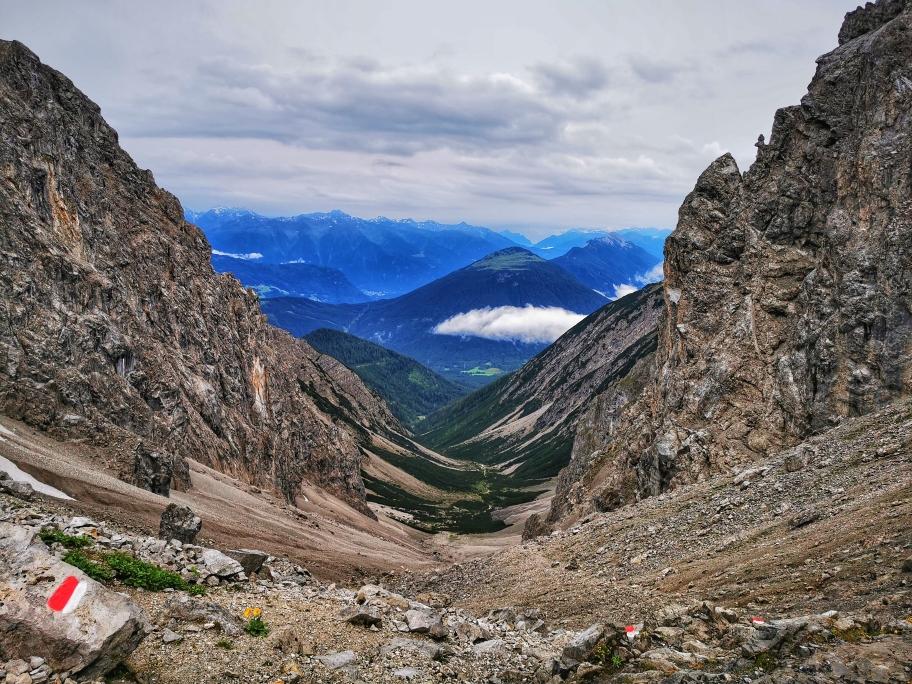 Der Blick ins Tal und den Abstiegsweg, im Hintergrund die schneebedeckten 3.000er des Sellrain