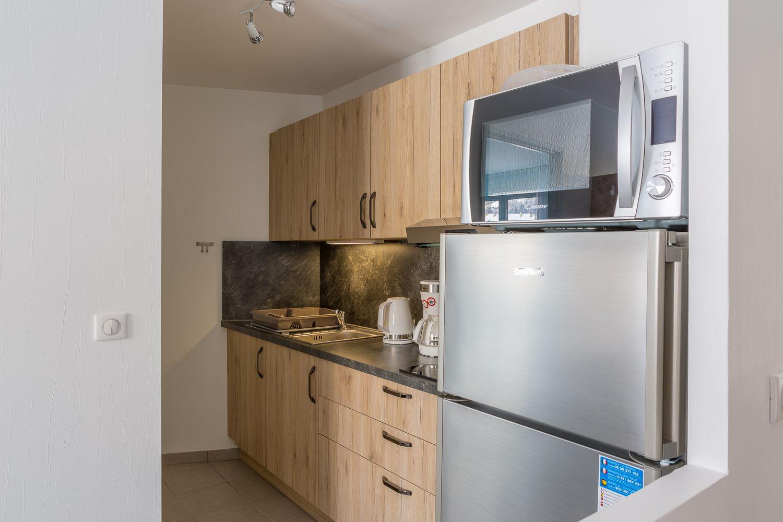 cuisine fonctionnelle, réfrigérateur avec partie congélateur, hotte, 3 plaques à induction