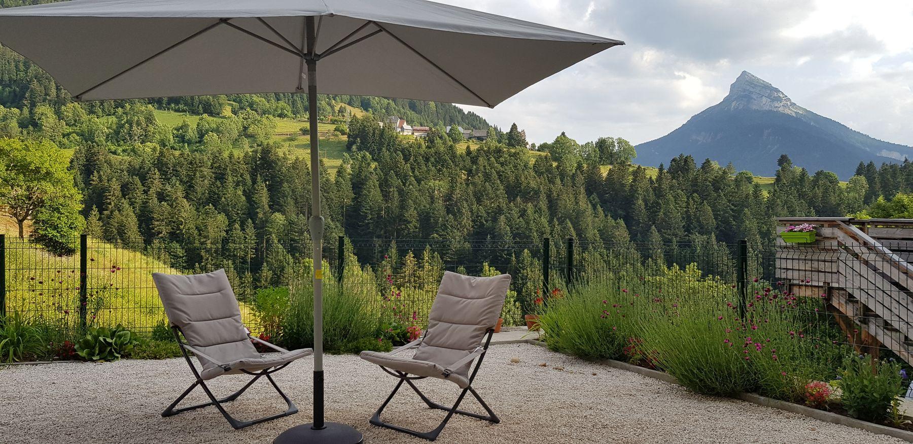 Terrasse fleurie entièrement close. Fauteuils, tables et chaises de jardin.