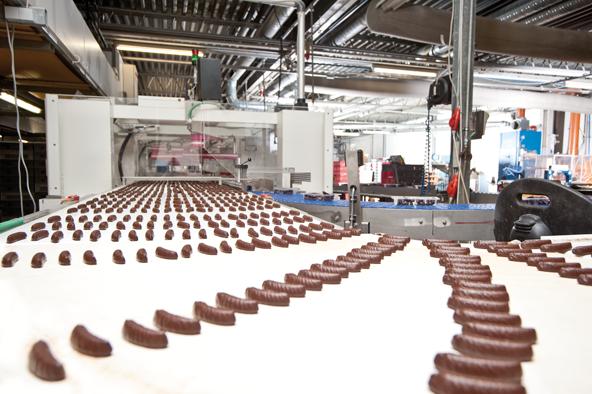 In einer Pickeranlage saugen Roboterarme die einzelnen Schoko-Geleebananenstücke mit Unterdruck an.