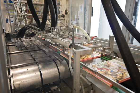 Die mit Schokolade befüllten Kunststoffeinlagen werden nun in die Kalenderhüllen geschoben. Eine Maschine verklebt noch die Laschen, damit die Plastikformen nicht wieder hinausfallen.