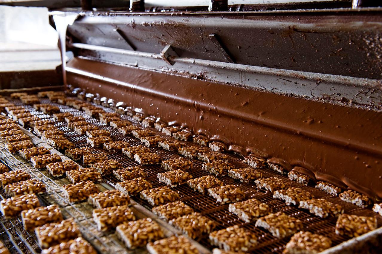 Die Sun Rice-Happen fahren auf einem Gitter unter einem Vorhang aus Vollmilchschokolade hindurch. Überflüssige Schokolade tropft nach unten ab.