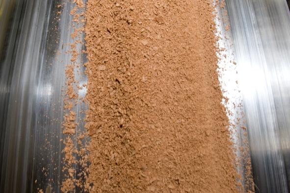 """Über ein Fließband gelangt die Schokolade in die Conche. Deren Name (vom spanischen """"Concha"""" = """"Muschel"""") rührt von der ursprünglichen Form des Troges."""