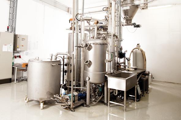 In einer futuristisch anmutenden Koch-Anlage werden die Zutaten zusammengemischt und gekocht.