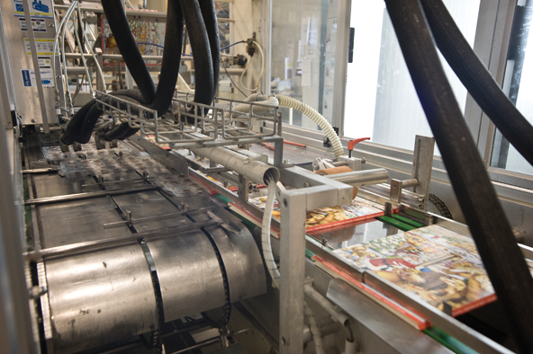 The plastic inserts filled with chocolate are now pushed into the calendar. A machine glues the flaps, so that the plastic forms will not fall out.
