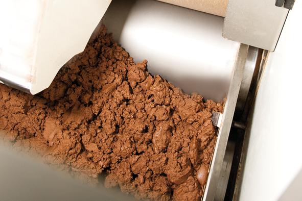 Es entsteht eine pulverige Masse, die anschließend von einem Fließband zur Conche transportiert wird.