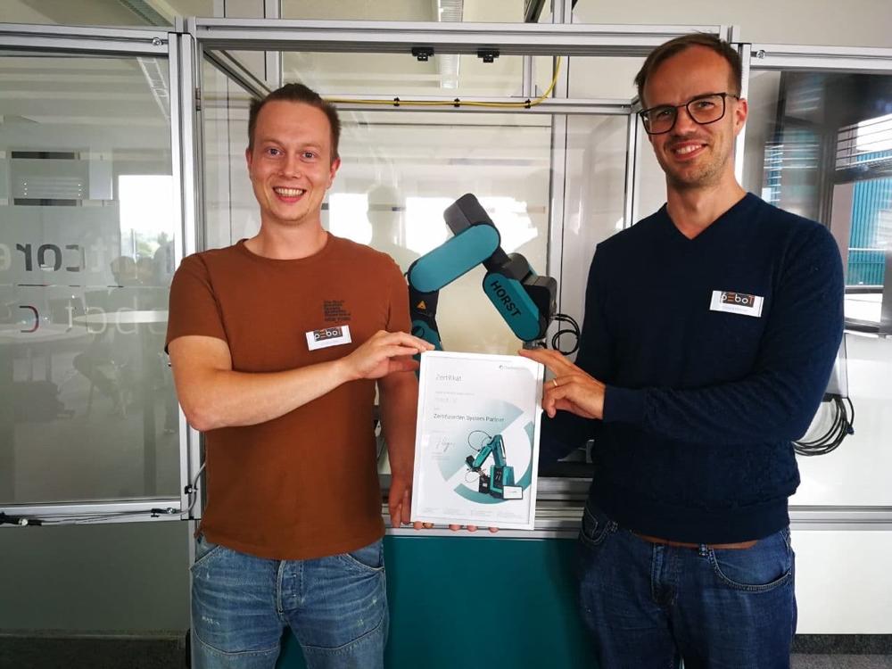 Christian Balz und Richard Petervari präsentieren die Urkunde zur Systempartnerschaft