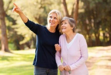 Senioren-Assistentin mit Senioren bei einem Spaziergang.