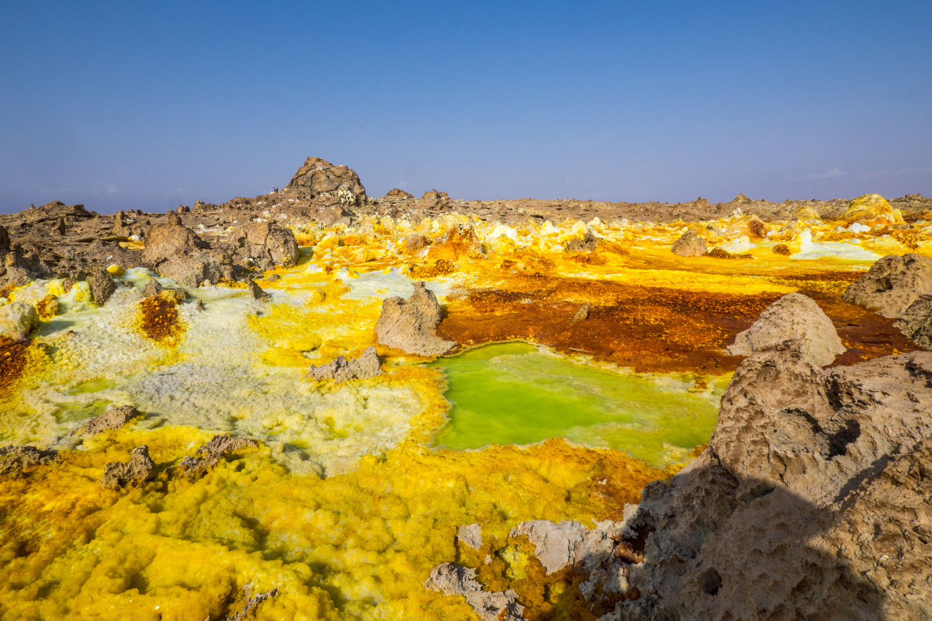 Dallol is a volcanic explosion crater in the Danakil Depression, northeast of the Erta Ale Range in Ethiopia. Numerous hot springs are discharging brine (solution of salt in water) and acidic liquid here. Widespread are small, temporary geysers which are