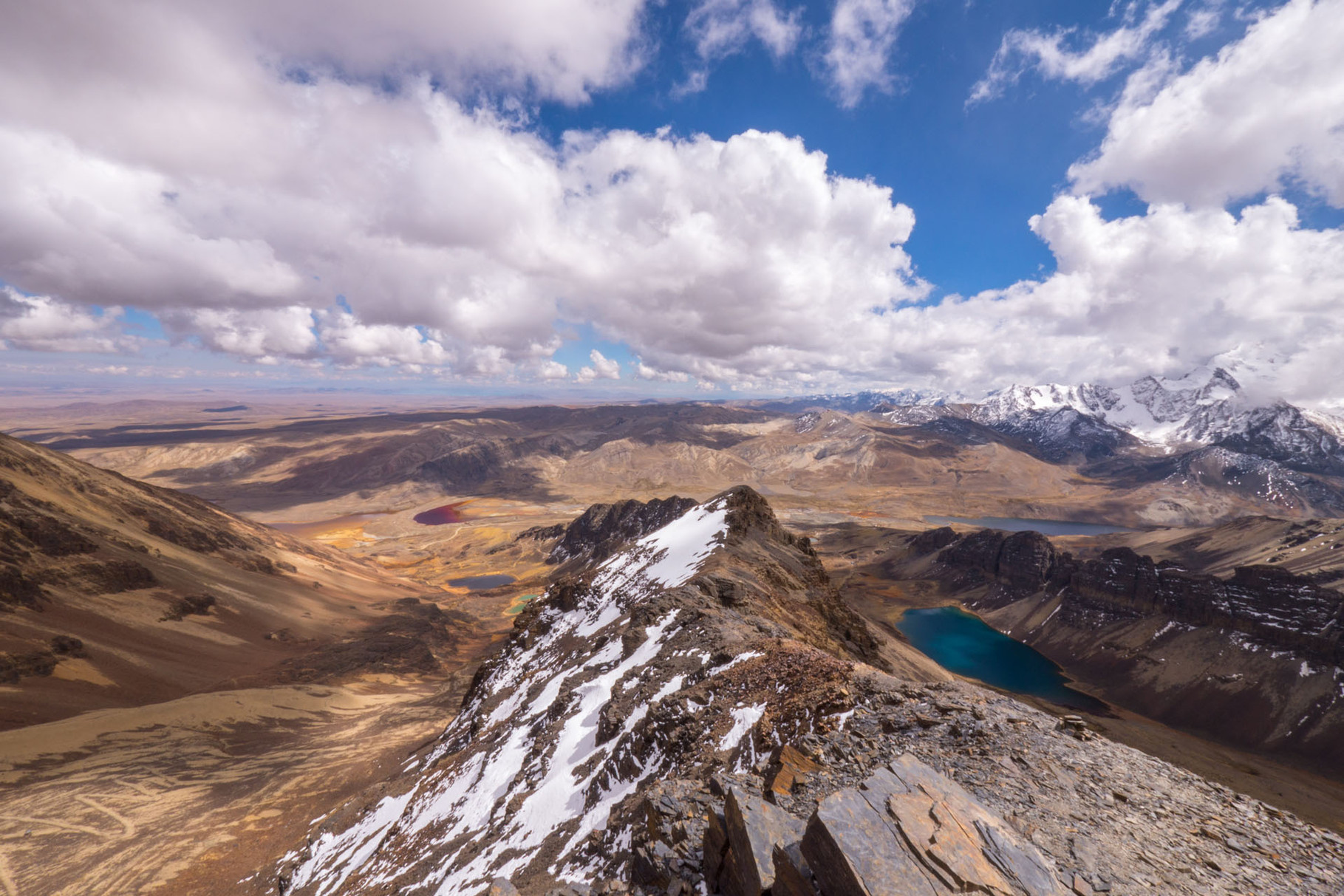 View from Chacaltaya (5400 masl) on various colored lagoons and cloud-covered Huayna Potosi