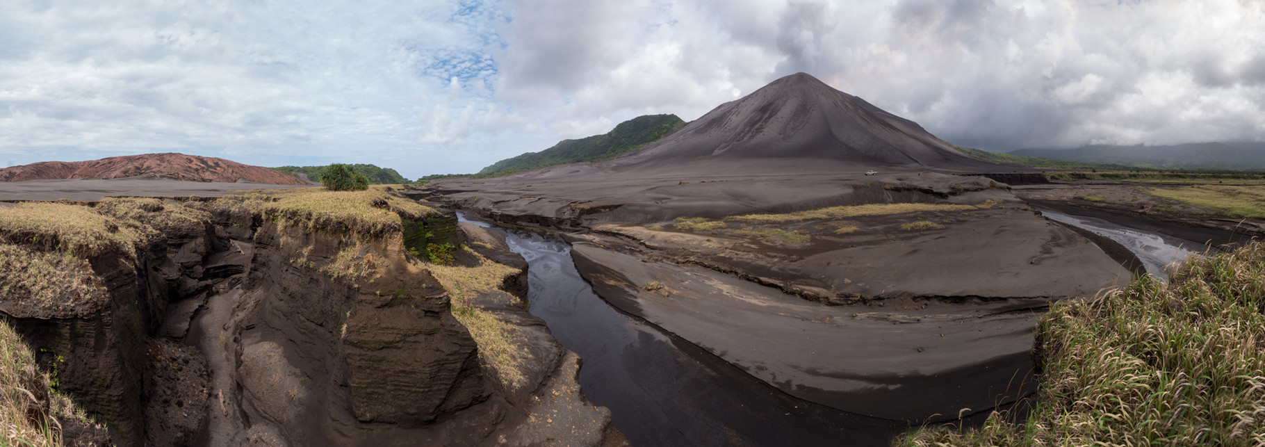Eroded ash plain and smoking Yasur volcano in the background , Tanna island