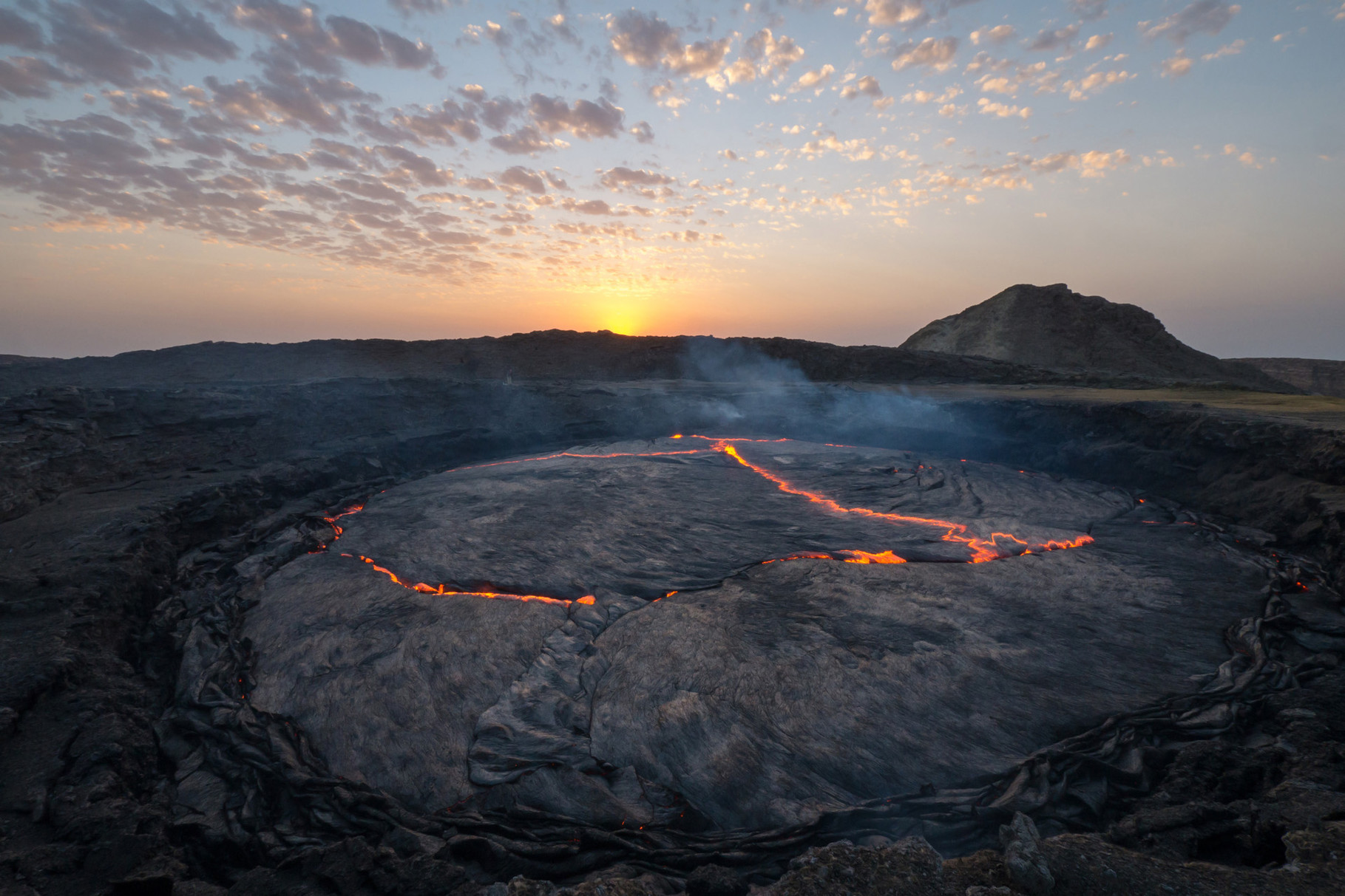 "Erta Ale: One of the very few lava lakes worldwide, and notably the longest-existing present since 1906.Erta Ale means ""smoking mountain"" in the local Afar language and its active pit is known locally as ""the gateway to Hell""."