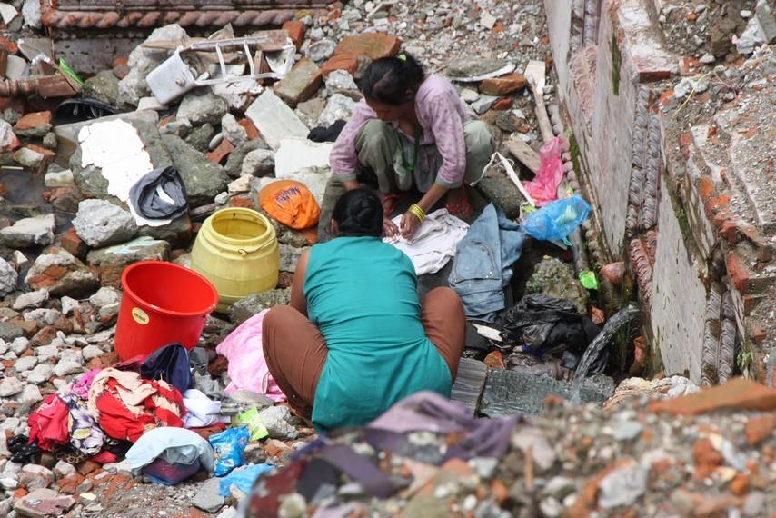 Femmes lavant leur linge dans les décombres
