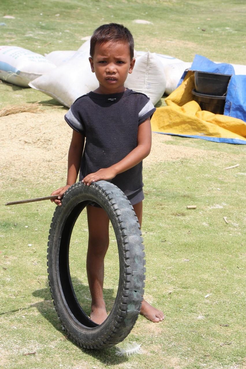 Enfant jouant avec un pneu sur la plage