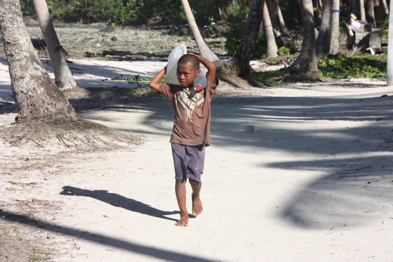 Enfant portant de l'eau