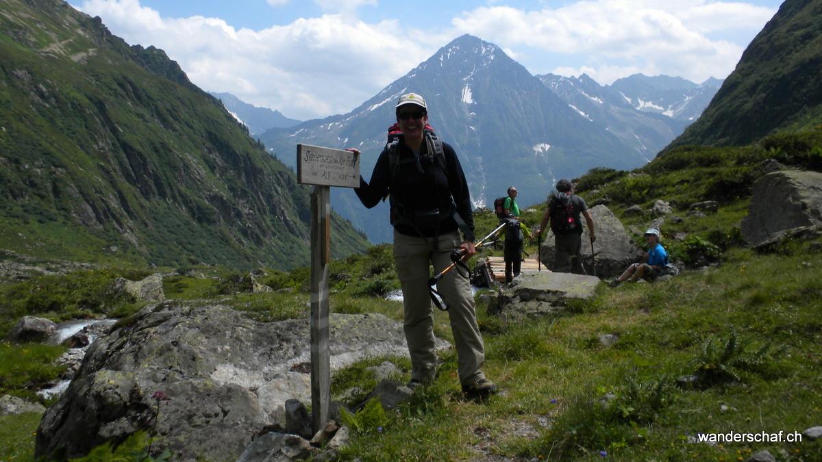 wir befestigen, den vom starken Föhn umgeblasenen Wegweiser zur Alp Furt mit Steinbrocken