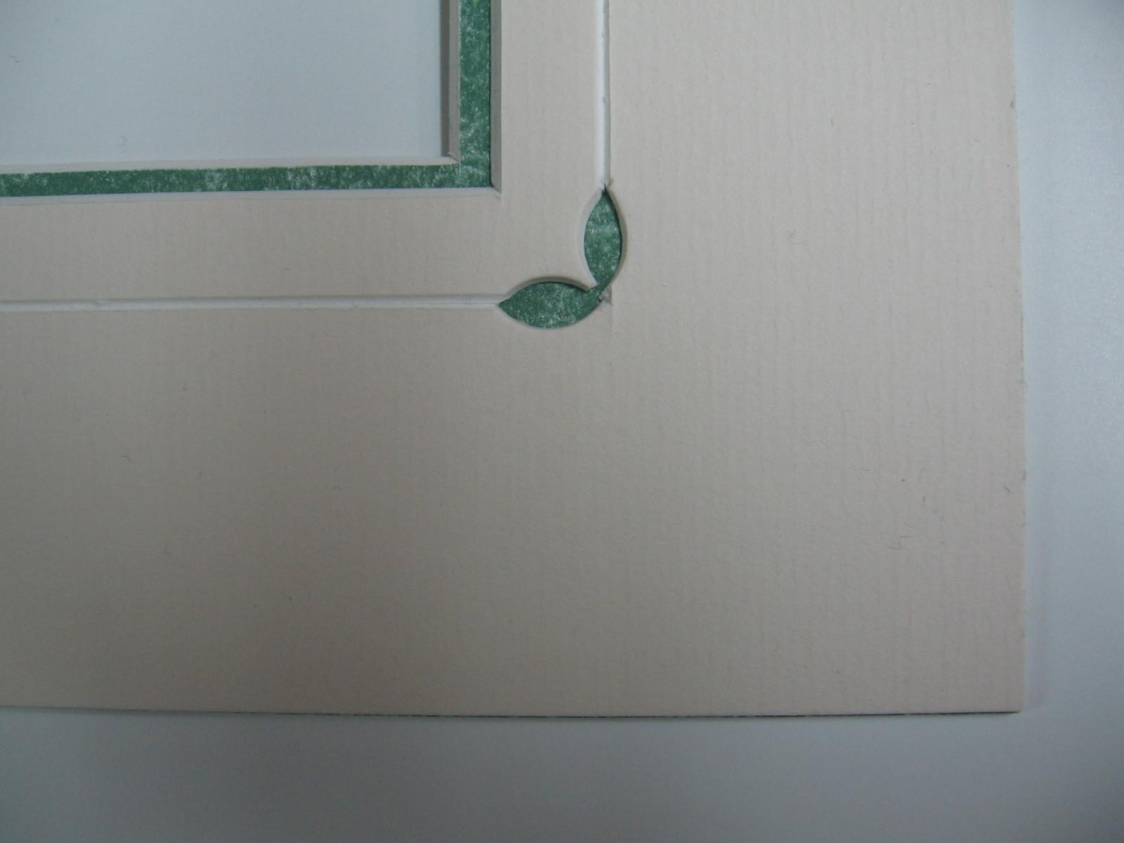 Particolare di un intarsio con un passepartout in cartoncino chiaro da cui ne traspare un altro in verde marmorizzato.