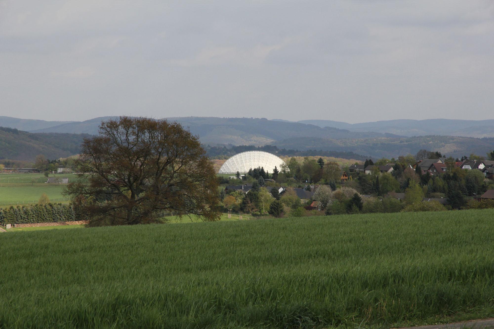 Nur der oberste Teil des Radioteleskops Effelsberg wird auf diesem Bild hinter dem Eifelörtchen Holzem sichtbar | Foto © Norbert Junkes | MPIfR