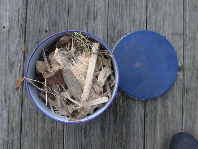 Holzresten, Tannenzapfen, Sagemehl etc in einen Blechdosen füllen.