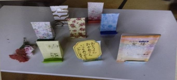 工作は父母へのプレゼントで牛乳パックと包装紙で「スマホ立て」「ブック立て」を作り、メッセージを書き渡しました