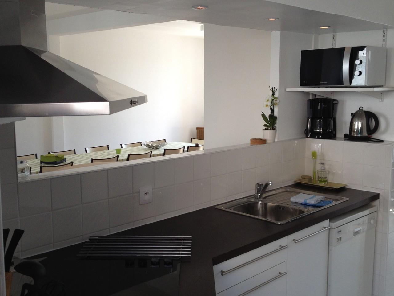 La cuisine aménagée et équipée avec micro onde, cafetière, plaques vitrocéramiques...