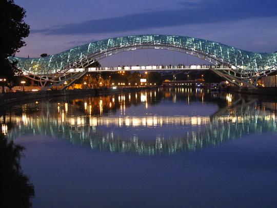 Die illuminierte Friedensbrücke von Tiflis überspannt die Kura