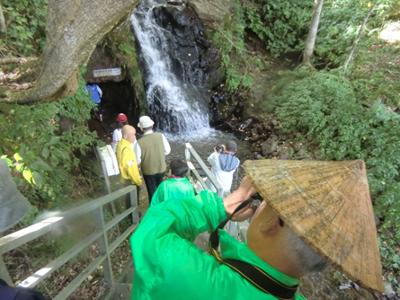 午後の初めは「矢ノ森金山跡・藤壺の滝」滝の脇に入口があり、長靴を履いていざ探検開始。いわいの里ガイドの会の伊藤さん(写真手前)が満を持して一閑張で作った菅笠(すげがさ)を被っていました。