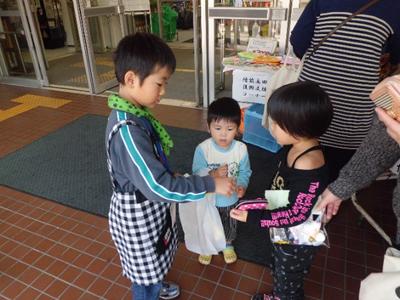 「子どもが子どものお店屋さんで買い物をするのをじっと見つめる子ども」の図