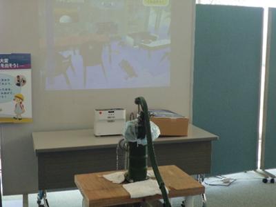 ゲリラ豪雨による床上浸水を仮想体験。手前の手押しポンプを動かしてリビング(映像)にたまった水をくみ上げます。ポンプの水は本物を使うというこだわり