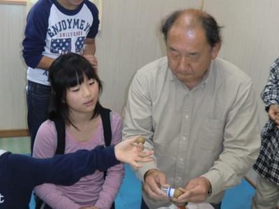 講師の先生(右側の男性)は関西弁を使って子供たちに親しみやすい雰囲気。「落っことしたらあかんで~。これだけ言っても必ず落っことす奴がおるんや。」先生の予言通りあちらこちらで「あーっ!」と叫んで球を落下させてしまう子供続出。