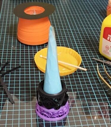 帽子の原型は、円を四分の一にカットした紙に、透明なプラ袋を貼って、円すいにまるめたもの。この原型に穴あきタイトサークルと細々したパーツを、交互にのせながら3段くらい積んでいく。